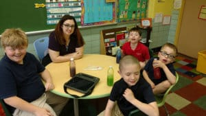 Students sitting with their teacher at St. Anthony's
